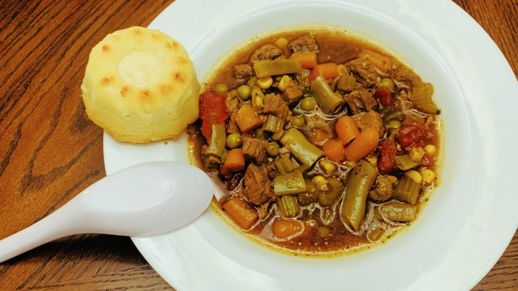 Bowl of Vegetable Beef Soup with a Biscuit